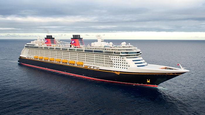 O Disney Dream, um navio com vários decks e uma proa imponente, em alto-mar.