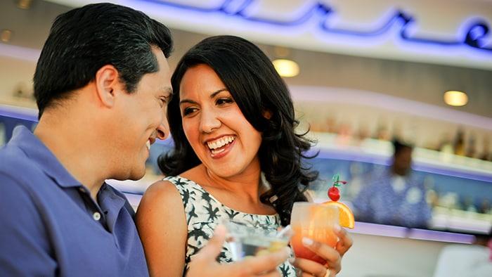 Um casal sorrindo e degustando drinks em um bar externo em um navio.