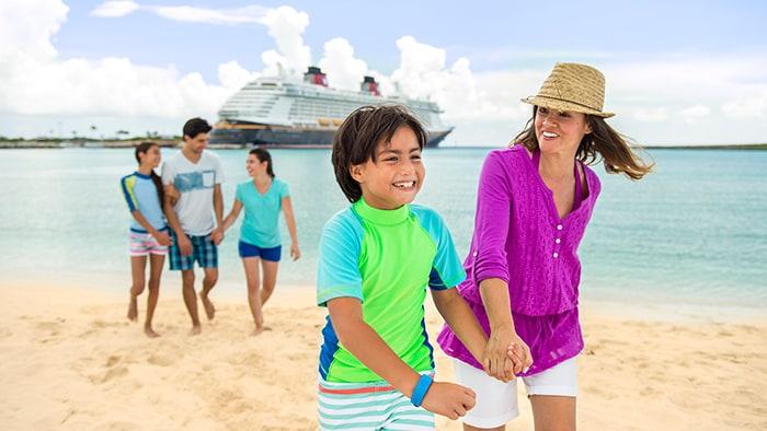 Una familia de cinco pasea en una playa y al fondo, un barco de Disney Cruise Line anclado en el muelle