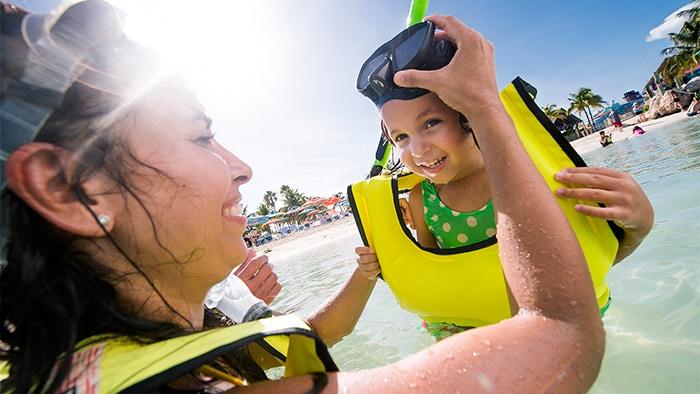 Una sonriente mamá ayuda a su niño a ponerse el snórkel en las aguas de la playa en Castaway Cay
