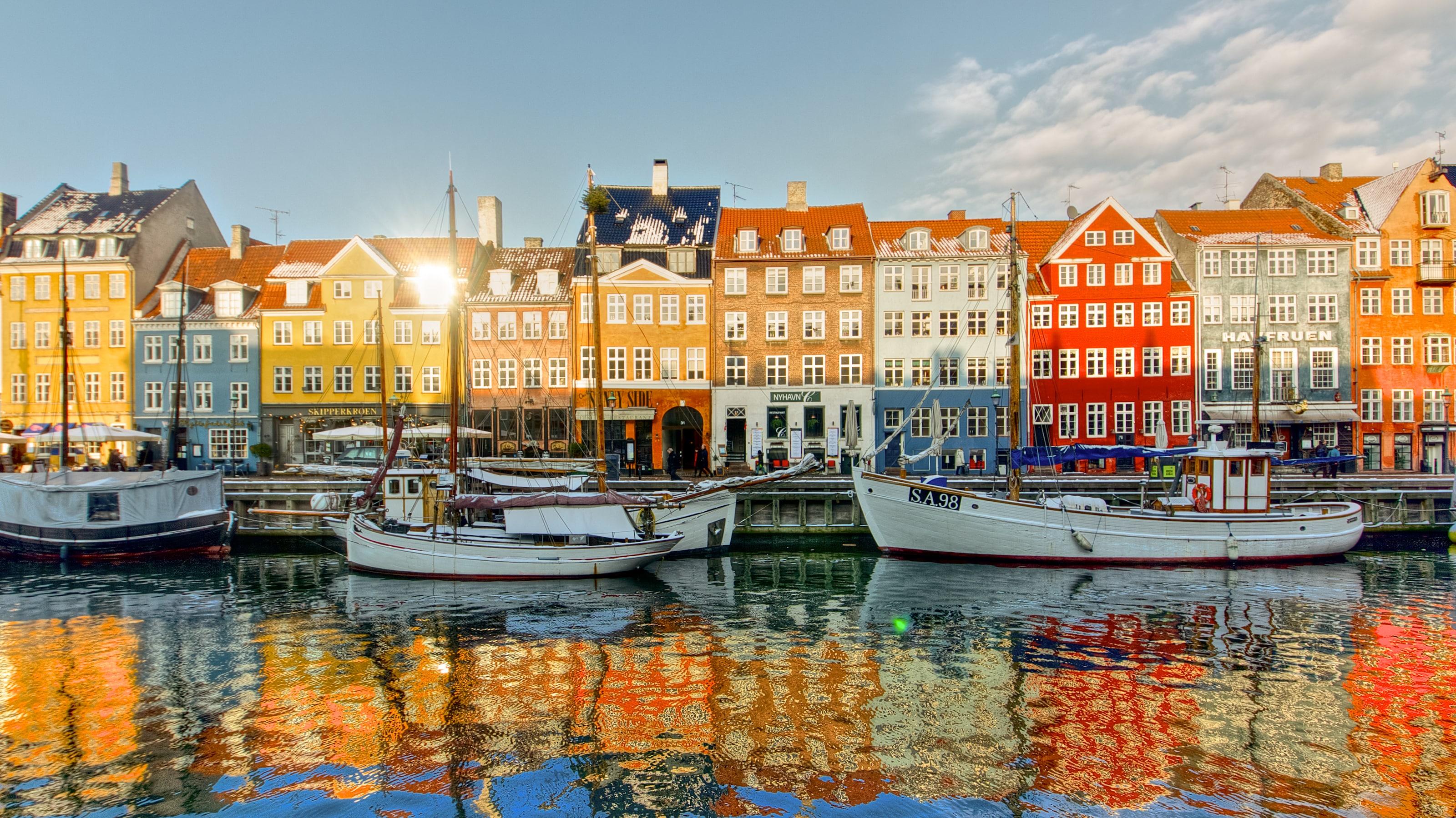 Des bâtiments colorés et des embarcations bordent un port de Copenhague, et se reflètent dans l'eau