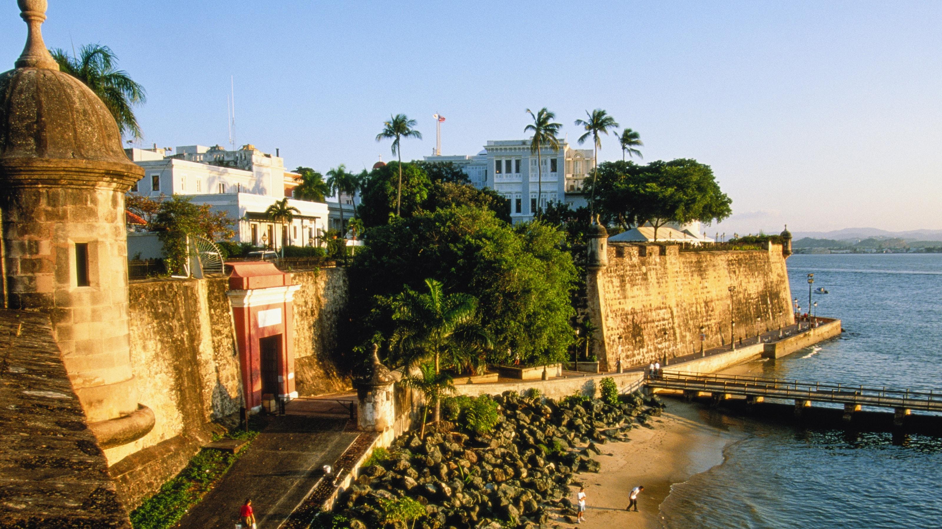 Pessoas caminham pelas construções do século 17 e pela muralha que circulam a Baía de San Juan.