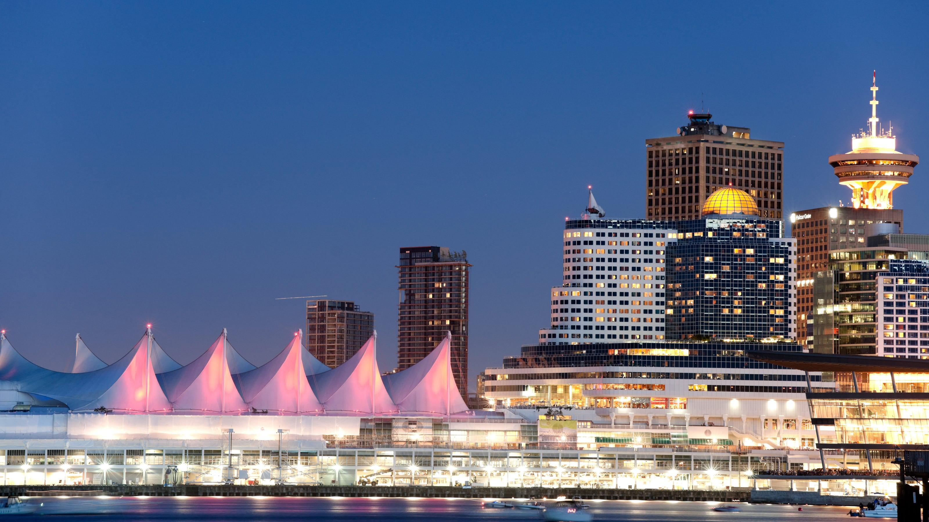 Uma sequência de telhados em forma de tenda à beira do porto de Vancouver, próximo a arranha-céus à noite.