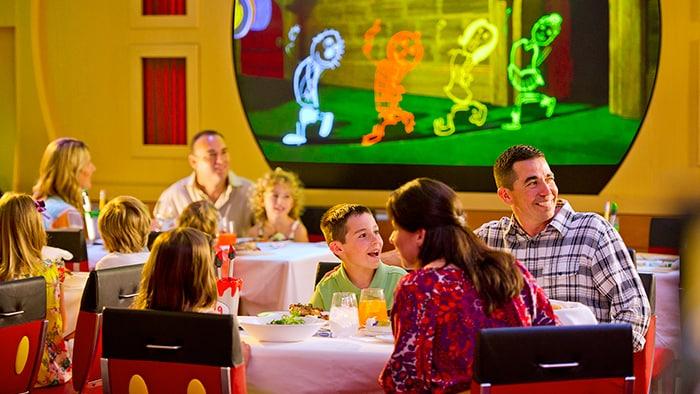 Familias en asientos con tema de Mickey Mouse disfrutan un espectáculo durante la cena que incluye animación