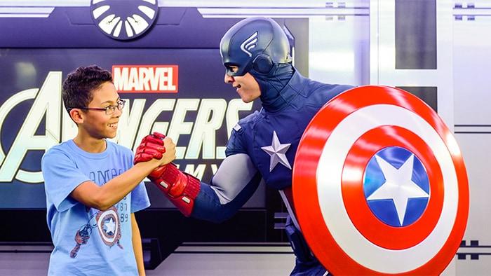 Capitão América cumprimenta um garoto em frente a uma placa da Marvel Avengers.