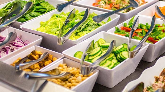 Vasilhas quadradas enfileiradas com opýýes de saladas e talheres para servir.