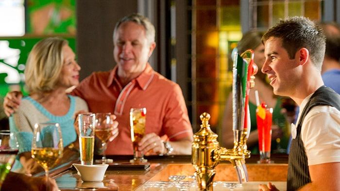 Um bartender usando colete conversa com um freguýs enquanto um casal saboreia seus drinks ao fundo