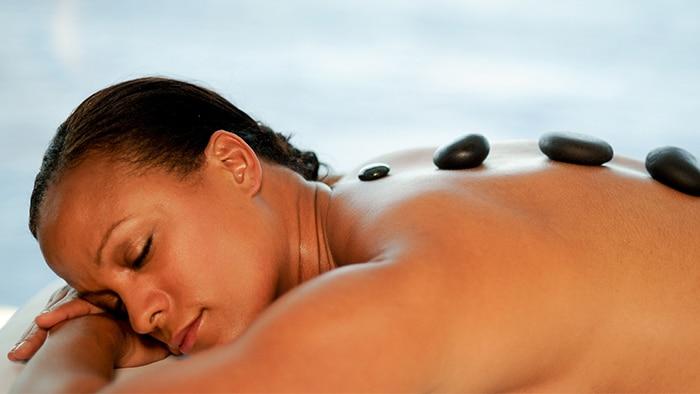 Deitada de bruýos, uma mulher relaxa durante uma terapia com pedras quentes.