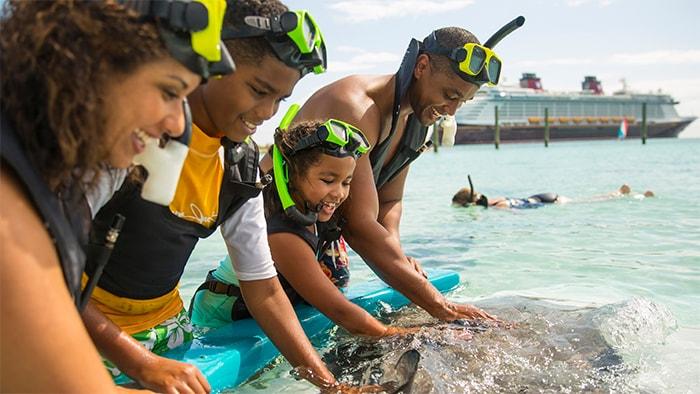 Una familia toma un descanso después de bucear con snórkel y acariciar delfines, y al fondo se ve un barco del crucero de Disney