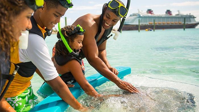 Uma família faz uma pausa no mergulho de snorkel para acariciar golfinhos, com um navio da Cruzeiro Disney Line ao fundo.