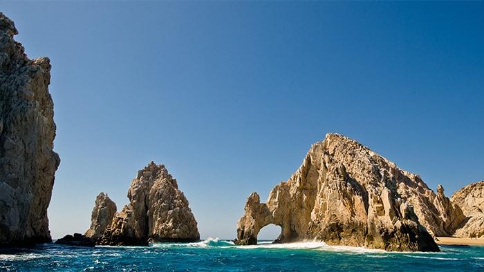 Uma estrutura rochosa esculpida pela natureza apresenta uma fenda grande o suficiente para a passagem de um pequeno bote.