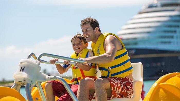 Pai e filho passeiam em triciclo aquático com um navio ao fundo.
