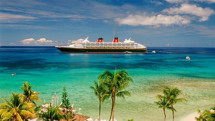 Un navire de croisière Disney près d'un rivage des Caraïbes, avec des palmiers et des drapeaux nautiques