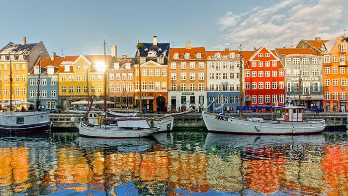 Des maisons de ville et des embarcations bordent un port de Copenhague, et se reflètent dans l'eau