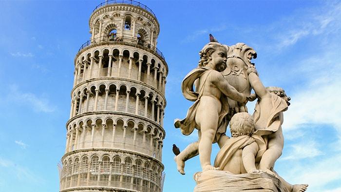 A Torre de Pisa e uma estátua de anjos ao lado dela.