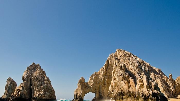 Une grande formation rocheuse dentelée avec une arche naturelle dans la Riviera mexicaine