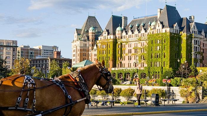 Une calèche devant The Empress Hotel, un grand bâtiment victorien où du lierre pousse sur le côté