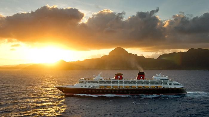 Un barco de Disney Cruise Line pasa navegando por montaýas donde se estý poniendo el sol