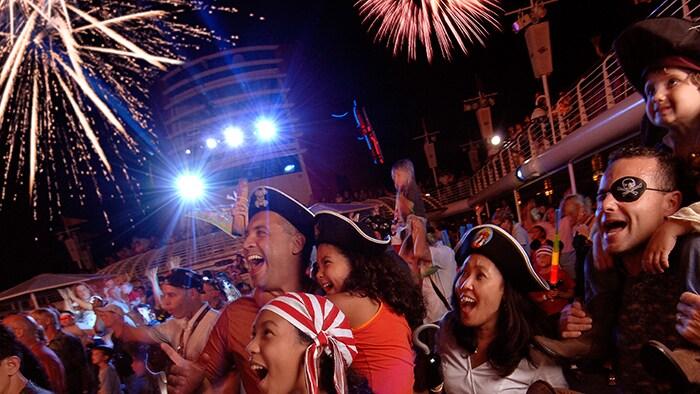 Durante una fiesta nocturna en la cubierta de un barco, una multitud de personas en disfraces de pirata ovacionan el espectáculo de fuegos artificiales