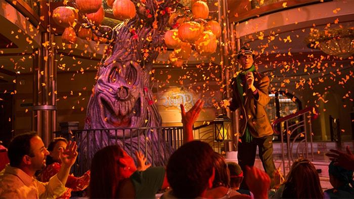 Em um show ao vivo, chove confete em um ator fantasiado de espantalho e no público, enquanto uma velha árvore sorri.