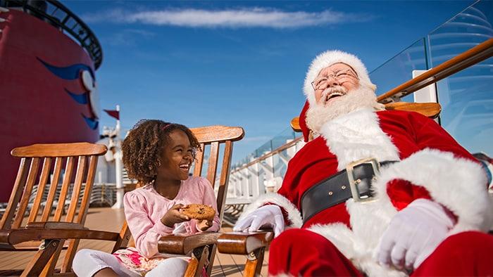 Uma garota oferece um biscoito para o Papai Noel, enquanto eles relaxam nas espreguiçadeiras de madeira do deck em um Cruzeiro Disney.