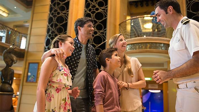 Un miembro de la tripulación interactúa con una familia de cuatro entre los diseños art nouveau del lobby de uno de los barcos