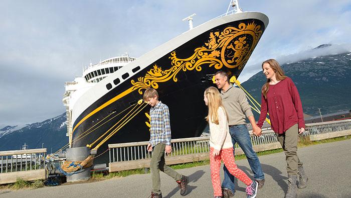 Une famille marche à côté d'un navire de croisière et près des montagnes