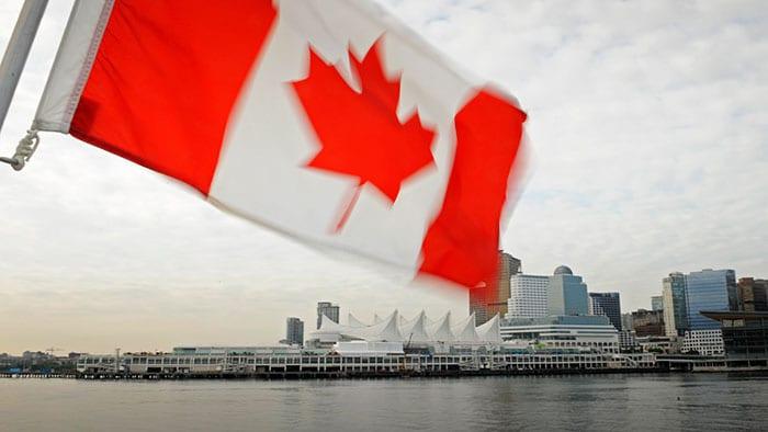 Un drapeau canadien à côté d'une ville côtière