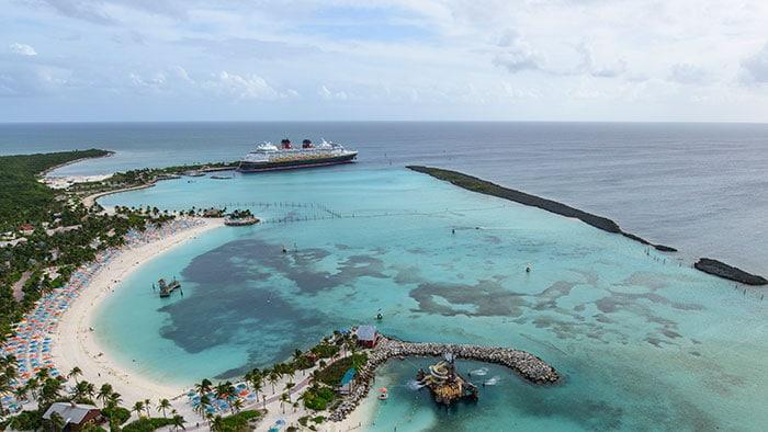 Un navire de croisière Disney près d'une île avec des bâtiments, des arbres et une plage bondée