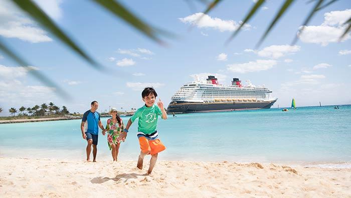 Un homme et une femme suivent un garçon qui court sur une plage près d'un navire de croisière