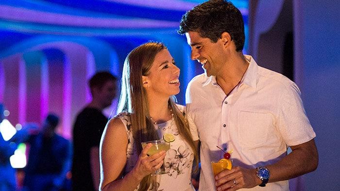 Un couple sourit en tenant des cocktails