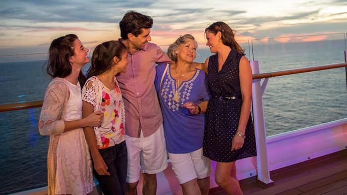 Une famille sourit sur le pont d'un navire de croisière