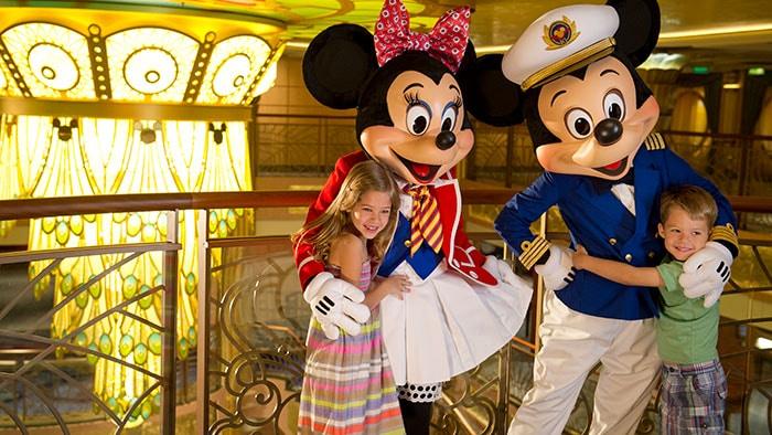 Deux enfants étreignent Minnie Mouse et Mickey Mouse