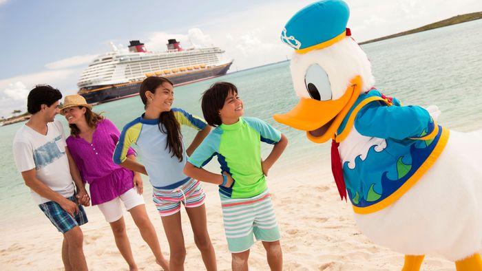 Une famille parle à Donald Duck sur une plage près d'un navire de croisière