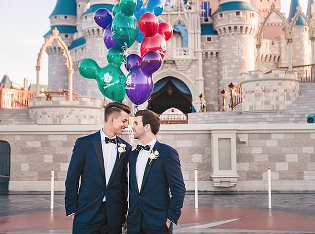 2 grooms posing in front of Cinderella Castle with Mickey Mouse balloons