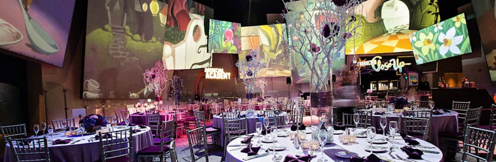 Round tables arranged in a room with large pictures showing scenes from 'Alice in Wonderland'