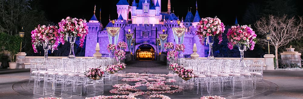 An aisle decorated with rose petals leading towards Sleeping Beauty Castle