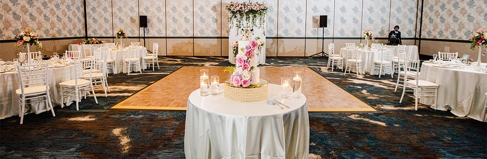 A cake table rests at the end of a dance floor in a reception hall