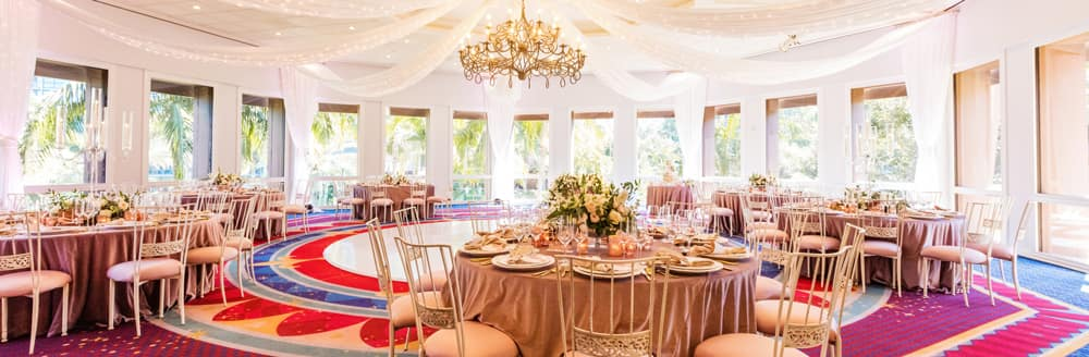 A chandelier hanging from the center of a room holding several round tables