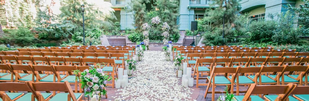 A courtyard with dining tables, chairs, flowers, hanging lights and trees