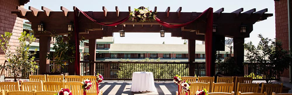 Rows of wooden chairs flank a petal covered aisle leading up to a pergola decorated with flowers and a floor length fabric swag