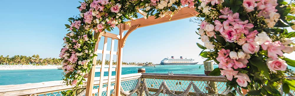 An archway decorated with a floral wreath on a deck in front of the ocean as a cruise ship sails nearby