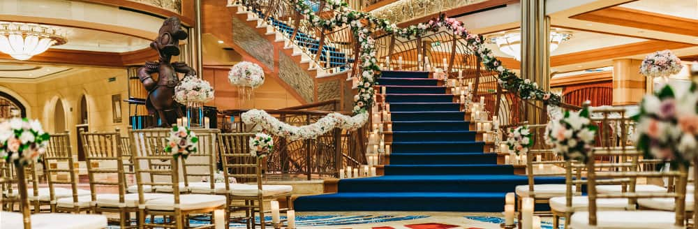 Two groups of chairs face an elegant staircase lined with flowers