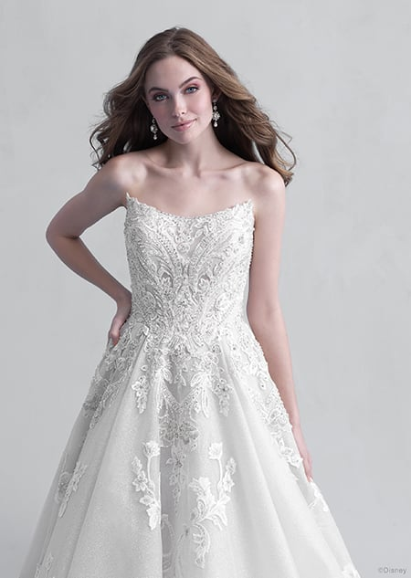 A woman stares down at the Aurora wedding gown from the 2021 Disney Fairy Tale Weddings Platinum Collection that she is wearing