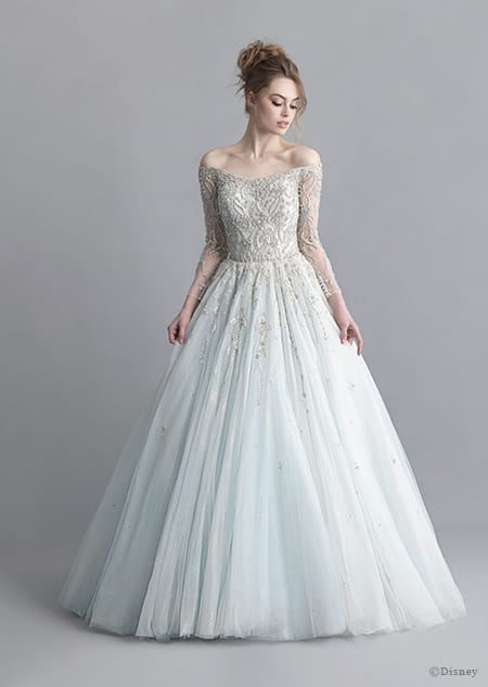 A woman stares down at the Cinderella wedding gown from the 2020 Disney Fairy Tale Weddings Platinum Collection that she is wearing