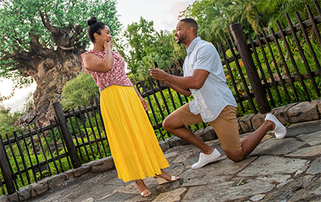 A man on one knee presents a ring to a woman, who covers her mouth in surprise, in front of the Tree of Life