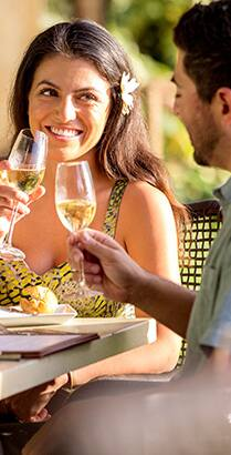 A man and woman toast one another with glasses of white wine