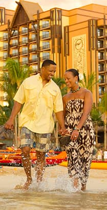 A man and woman hold hands while walking on the beach at Aulani