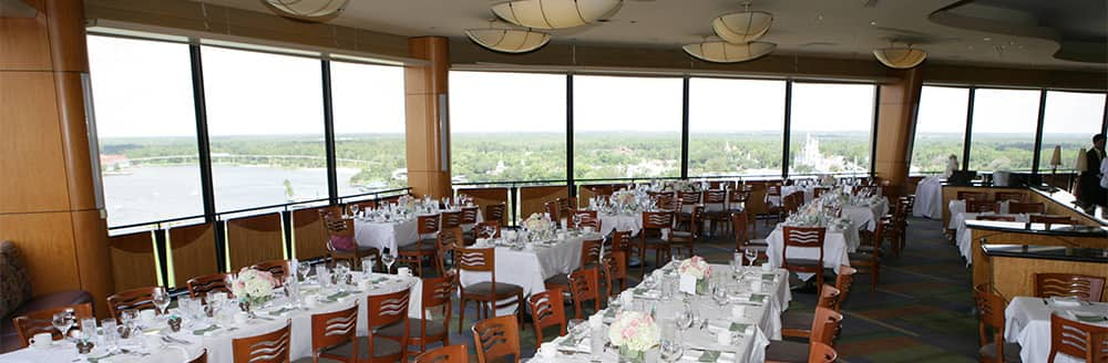 Long rectangular tables surrounded by chairs in room with large windows
