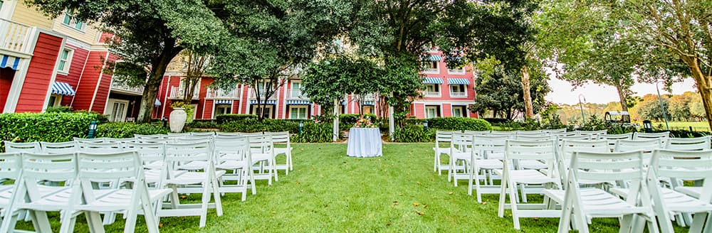 An aisle leading to a small round table on a lawn with trees in the background